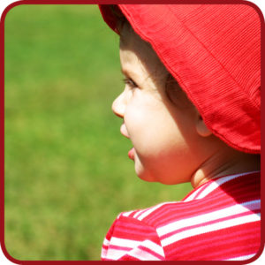 een kind buiten met een hoed op in de zon