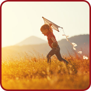 kind speelt buiten met een vlieger